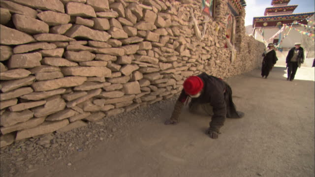 A Tibetan man prays in a street.