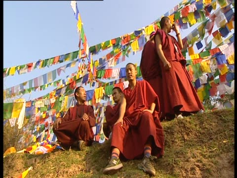 Tibetan monks sit on a hill surrounded by colorful prayer flags as birds call