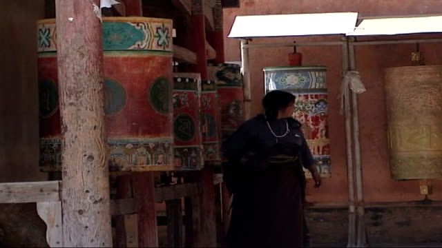 buddhist temple and monks ext visitors worshippers children and monks in temple courtyard enclosure including prayer wheels decorating inner temple... - traditionally tibetan stock videos & royalty-free footage