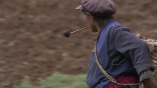 a tibetan woman smokes a pipe as she walks with a large basket on her back. - tabakwaren stock-videos und b-roll-filmmaterial