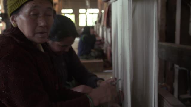 tibetan woman weaving rugs at tibetan refugee center in slow motion - tessere video stock e b–roll