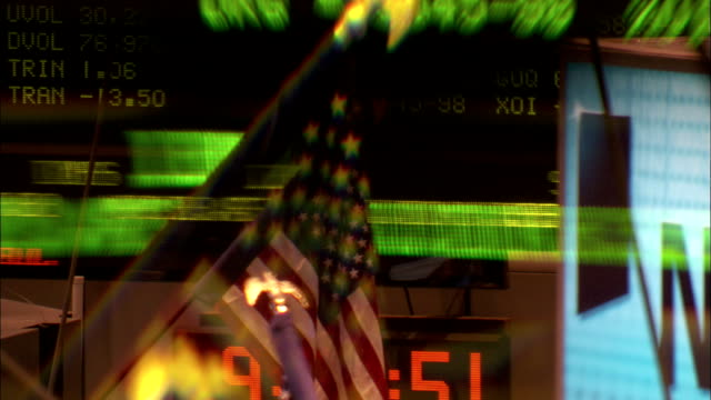 ticker tape quotes of stock prices run behind an american flag at the new york stock exchange. available in hd. - ticker tape stock videos and b-roll footage