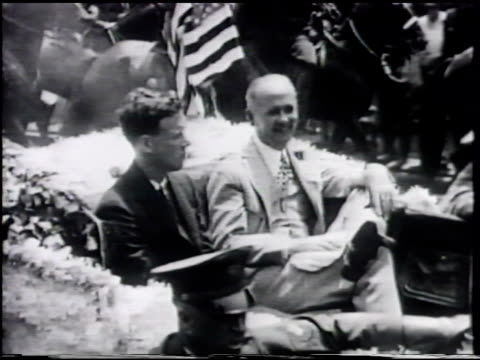 tickertape falling w/ buildings bg td ws parade ws american aviator charles a lindbergh riding in convertible car w/ unidentified man crowd waving... - 1927 bildbanksvideor och videomaterial från bakom kulisserna