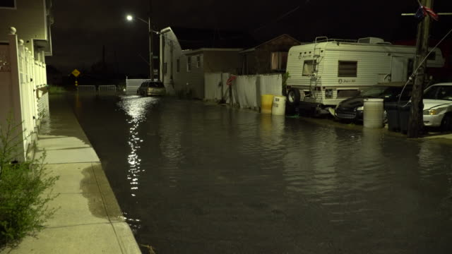 Tidal flooding from Jamaica Bay submerges a residential street at night in Queens New York during high tide cycle