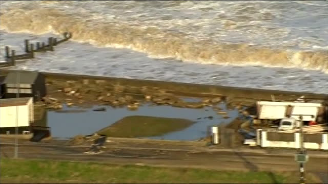 vídeos de stock, filmes e b-roll de air views of the norfolk coastline air views / aerial large waves breaking against the shoreline at walcott / flooded field between walcott and... - 2013