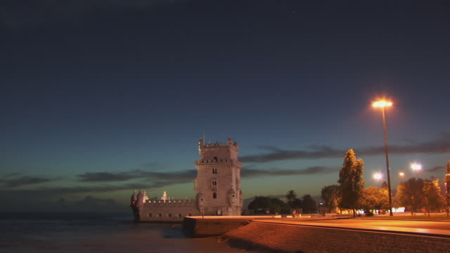 T/L WS Tide lapping against retaining wall near Torre de Belem at dusk / Lisbon, Portugal