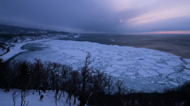 tide retreats from coastal sea ice as sun sets. - tide stock videos & royalty-free footage