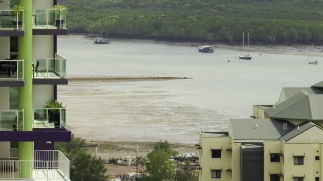 WS ZO T/L Tide rushes into Darwin harbor, high-rise building in foreground / Darwin, Northern Territory, Australia.