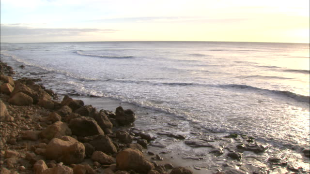 tides lap up on a rocky beach. - argentina stock videos & royalty-free footage