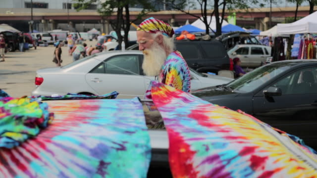 tie dye artist yano harris displays tie-dyed shirts he made to sell on shakedown street in parking lot lot b during the grateful dead's fare thee... - shirt and tie stock videos & royalty-free footage