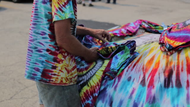 tie dye artist yano harris displays tiedyed shirts he made to sell on shakedown street in parking lot lot b during the grateful dead's fare thee well... - t shirt stock videos & royalty-free footage