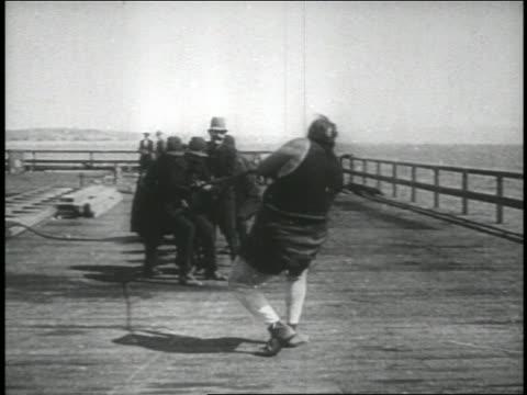 b/w 1914 tied man (fatty arbuckle) pulling keystone kops across pier near ocean / feature - dragging stock videos & royalty-free footage
