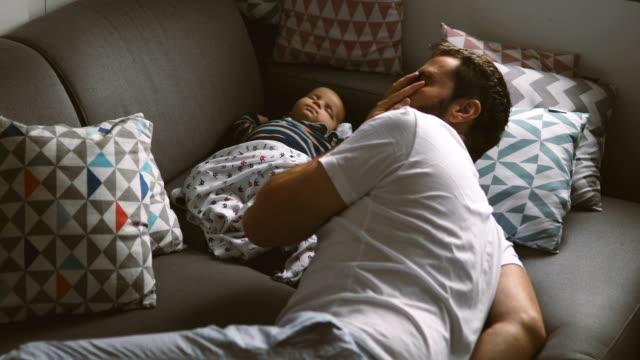 vídeos y material grabado en eventos de stock de dad en niveles de estiramiento y continuar dormir en el sofá con su bebé - padres amos de casa