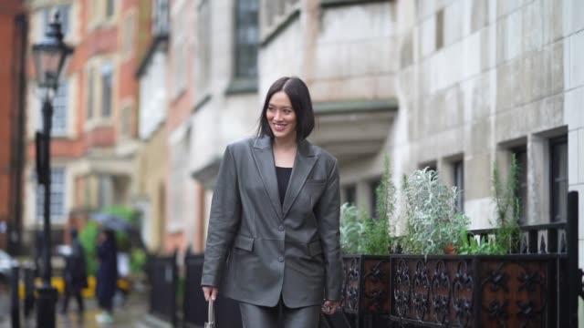 tiffany hsu wears a gray shiny oversized blazer jacket, suit pants, pointy shoes, leather bags, during london fashion week fall winter 2020 on... - kostym bildbanksvideor och videomaterial från bakom kulisserna