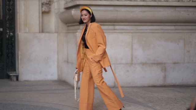 tiffany hsu wears an orange hairband, a burgundy top, an orange pantsuit with high waist flare pants, outside paco rabanne, during paris fashion week... - street style stock videos & royalty-free footage
