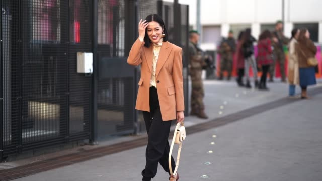 tiffany hsu wears earrings, an orange blazer jacket, a chloe bag, black pants, shoes, a shirt, outside chloe, during paris fashion week womenswear... - street style stock videos & royalty-free footage