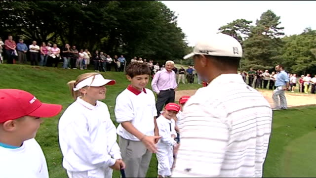 tiger woods interview; woods greets child golfers young girl sinking putt woods congratulates her - sportlerin stock-videos und b-roll-filmmaterial