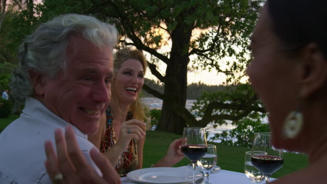 tigh shot of three friends laughing while having a dinner during sunset - social gathering stock videos & royalty-free footage