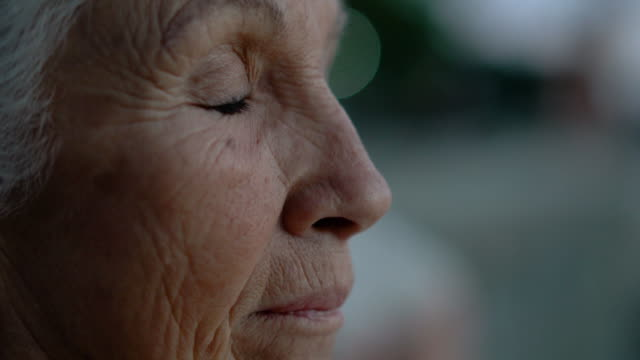 Tight CU and side shot view of a senior lady turning her face to the camera in a natural daylight.