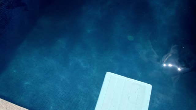 Tight overhead pan across empty open air swimming pool from diving board