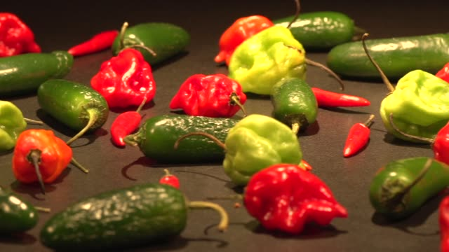 a tight panning shot of multiple types of hot peppers on a dark surface hot peppers on january 06 2014 in new york new york - peperone video stock e b–roll