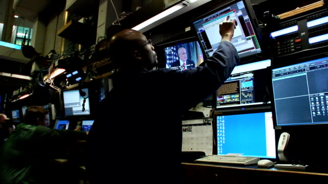 tight shot eye-level view of trader working an watching henry m. paulson on tv monitor referring to the auto industry on trading floor of new york... - manövrera bildbanksvideor och videomaterial från bakom kulisserna