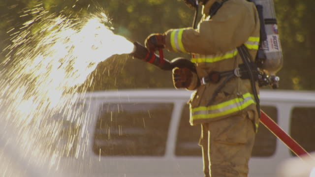 tight shot nozzle spraying water which is held by a firefighter. - hold me tight stock videos & royalty-free footage