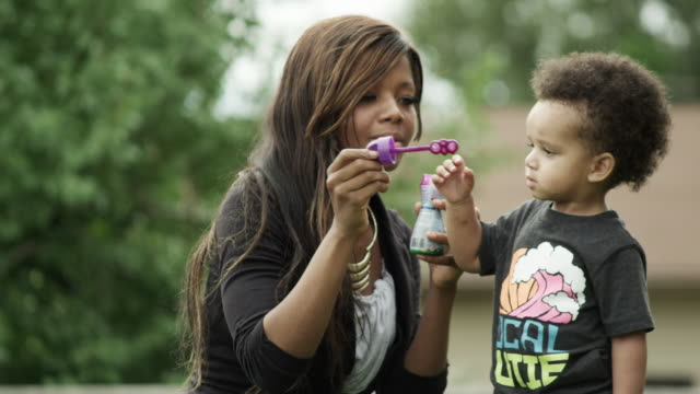 tight shot of a mother and son in the backyard blowing bubbles. - hold me tight stock videos & royalty-free footage