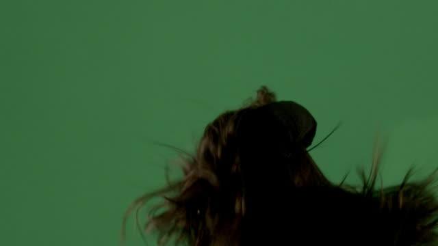 vidéos et rushes de tight shot of a near silhouetted woman on green screen dancing. - seulement des jeunes femmes