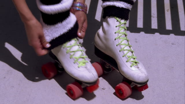 tight shot of a woman adjusting leg warmers on her roller skates. - leg warmers stock videos & royalty-free footage