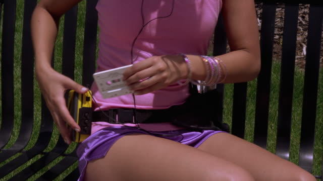 tight shot of a woman placing a cassette in a walkman on a park bench. - stereo personale video stock e b–roll