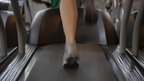 tight shot of a woman running on a treadmill - treadmill stock videos & royalty-free footage