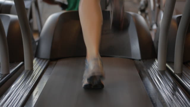 Tight shot of a woman running on a treadmill