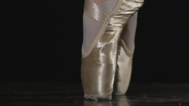 tight shot of ballerina feet moving from flat foot to on point. - auf den zehenspitzen stock-videos und b-roll-filmmaterial