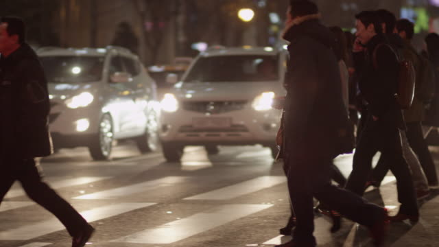 tight shot of crowds of people crossing a busy street at night in seoul - ソウル点の映像素材/bロール