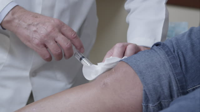 tight shot of doctor making injection to patient's knee. - menschliches knie stock-videos und b-roll-filmmaterial