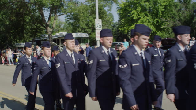 Tight shot of formation of military Air Force personnel marching down the street in small town parade.