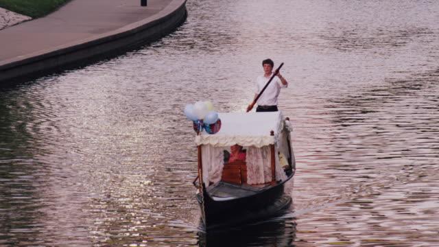 vídeos de stock e filmes b-roll de tight shot of gondola floating peacefully down a stream and the gondola operator waves - só um homem de idade mediana