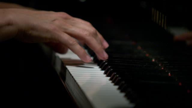 tight shot of hands playing the piano. - ピアノ点の映像素材/bロール