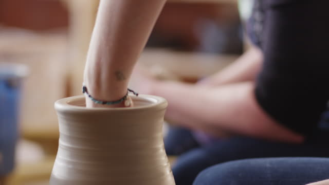 Tight shot of hands sculpting a clay vase on a potters wheel.