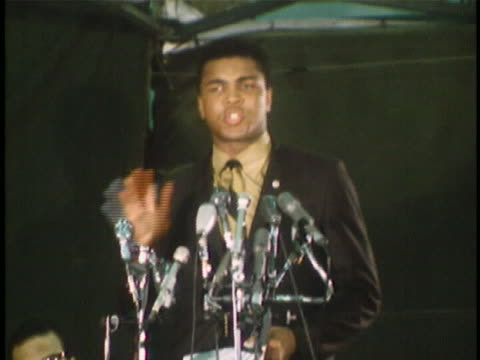 """tight shot of muhammad ali standing at lectern with many microphones. he looks up from his prepared remarks and says: """"they say that actually, every... - アリ点の映像素材/bロール"""
