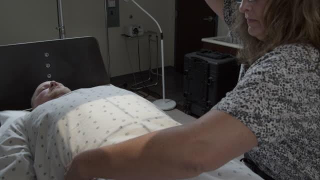 tight shot of nurse preparing a scan of man's stomach. - untersuchungskittel stock-videos und b-roll-filmmaterial