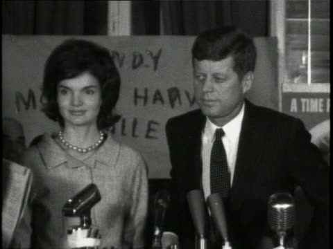 tight shot of senator john f. kennedy standing at a lectern alongside wife jackie kennedy. there are microphones in front of him, and signs and... - jackie kennedy stock videos & royalty-free footage