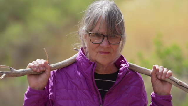 tight shot of serious elderly lady out in nature holding dead tree branch - menschliches gelenk stock-videos und b-roll-filmmaterial