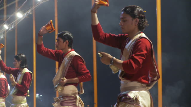 Tight shot of several men in a line performing an incense offering to the Ganges.
