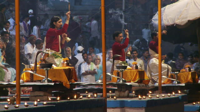 Tight shot of several men ringing bells and waving incense sticks as part of a ceremony.