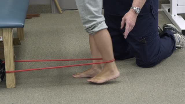 vídeos y material grabado en eventos de stock de tight shot of therapist working with woman for elastic band exercises. - articulación humana