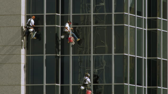 Tight shot of three window washers on lines washing a highrise building.