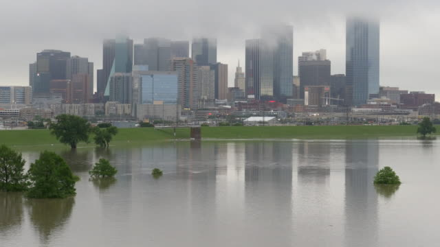 t/l tight shot of trinity river flood waters up against protective levee and dallas downtown buildings engulfed in clouds - levee stock videos & royalty-free footage