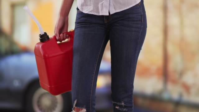 tight shot of waist of woman with gasoline canister standing by car in street - hold me tight stock videos & royalty-free footage